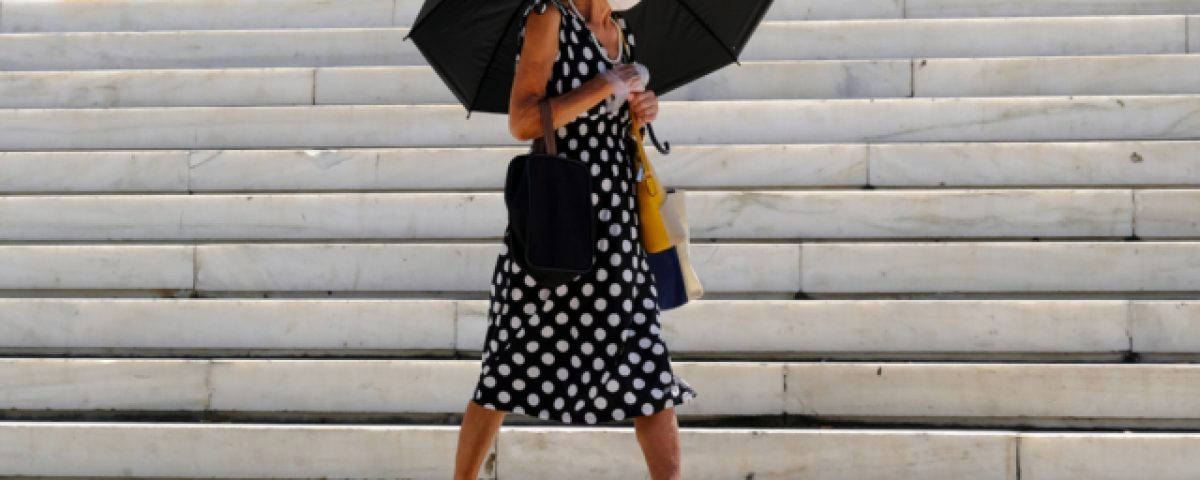A,Woman,Holds,An,Umbrella,During,A,Heatwave,,In,Athens,